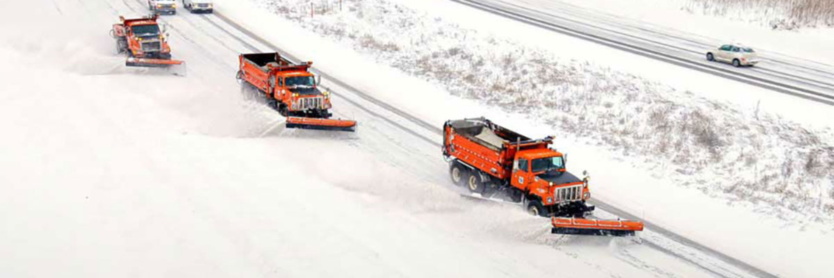 MnDOT plow clearing snow from a roadway.